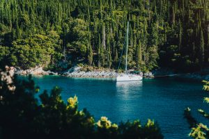 White sail boat yacht moored in the bay of Foki beach with cypress trees in background, Fiskardo, Cefalonia, Ionian, Greece.